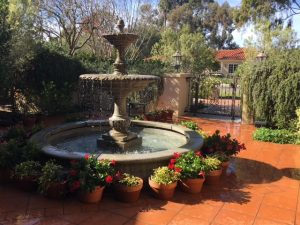 Large Fountain in gated yard with clay tile